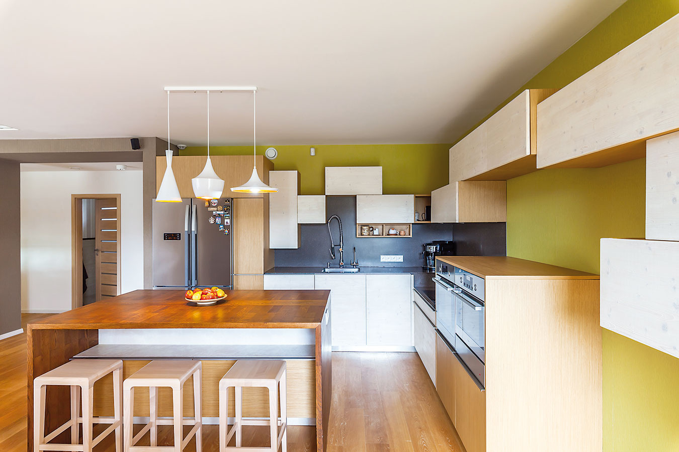 Kuchyňa určite nepôsobí štandardne ani chladne. Vďačí za to nápaditému usporiadaniu aprírodným materiálom (drevené dvierka linky sú kefované anamorené, ich povrchovú úpravu si vzal na starosť domáci pán).