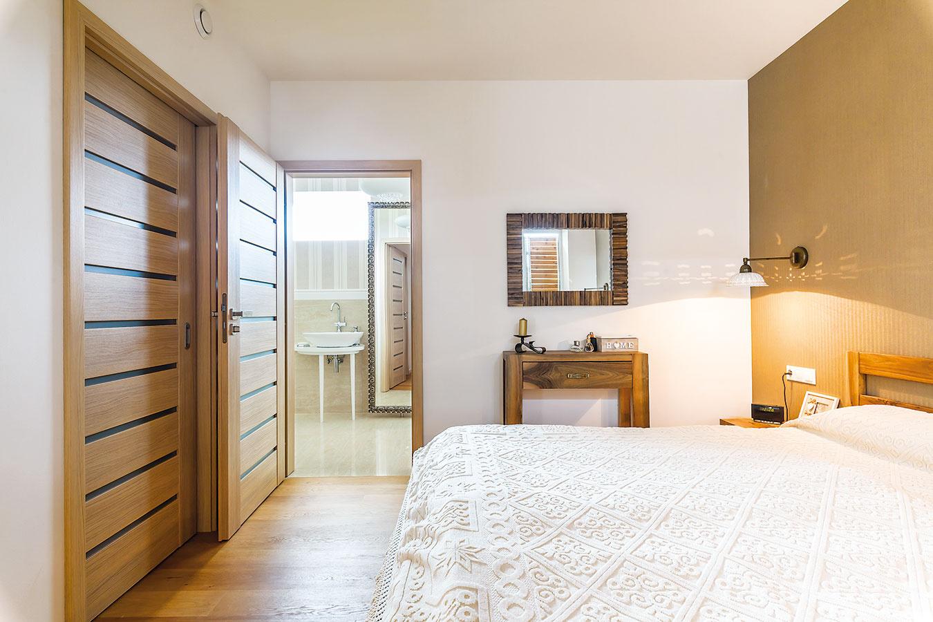 Z hlavnej spálne je prístupný šatník aj samostatná kúpeľňa. Aj tu sa prírodné materiály afarby postarali opríjemnú, pokojnú atmosféru.