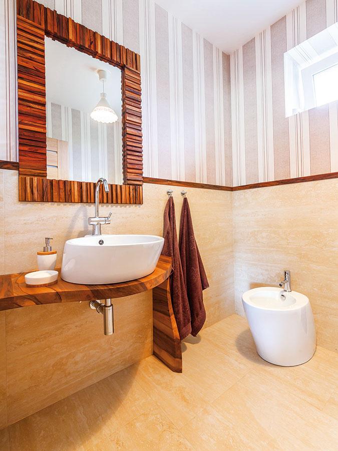 Hosťovskú kúpeľňu vtlmených neutrálnych tónoch, aké sú typické pre celý dom, oživuje orechové drevo svýraznou kresbou.