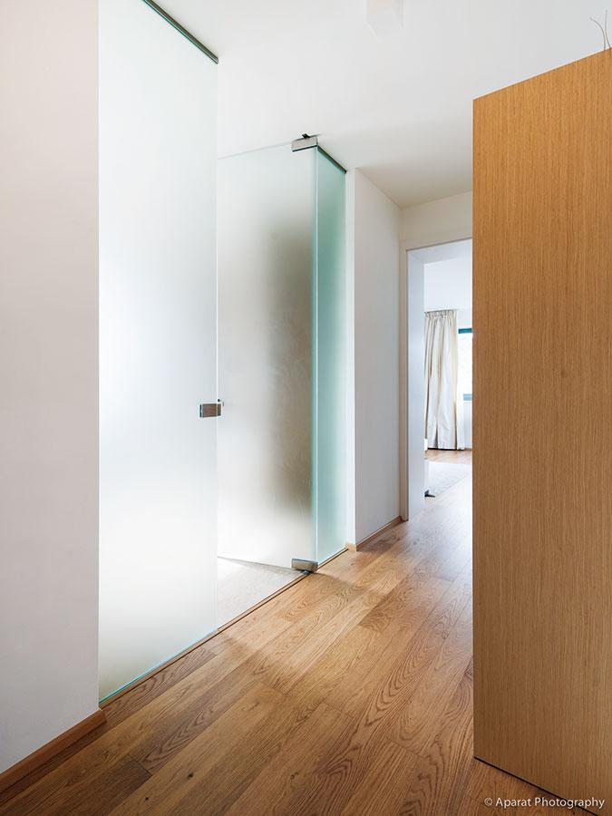 Stena zmliečneho skla oddeľuje od chodby kúpeľňu, kde sa žiada viac súkromia. Nepriehľadné, ale priesvitné sklo pritom splnilo aj svoju druhú úlohu – prepustiť svetlo do chodby.