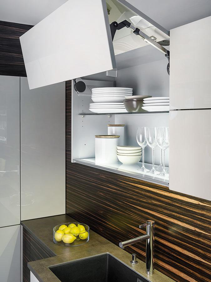 Otváranie horných skriniek pomocou výklopných dvierok je vhodné najmä do malých kuchýň. Jednotlivé poličky sa dajú ľahko prispôsobiť výške porcelánu či skla.