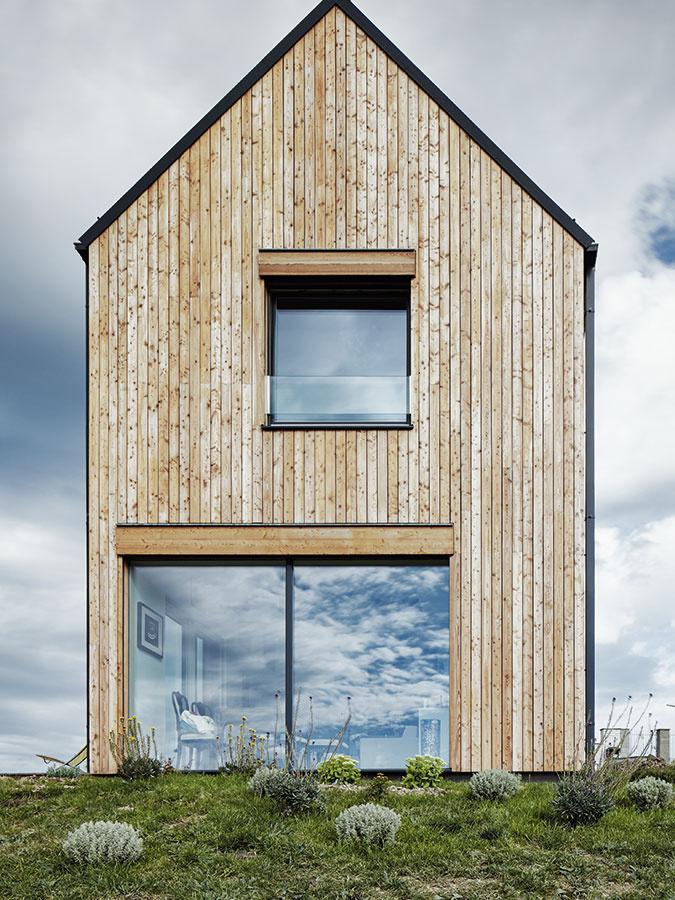 Jednoduchá forma. Čistý tvar domu nenarúšajú žiadne zbytočné detaily ako presah strechy či materiálová rôznorodosť. Fasáda je zo zvislých dosiek zčerveného smreka, ukladaných len jednoducho na zraz smalou medzerou.