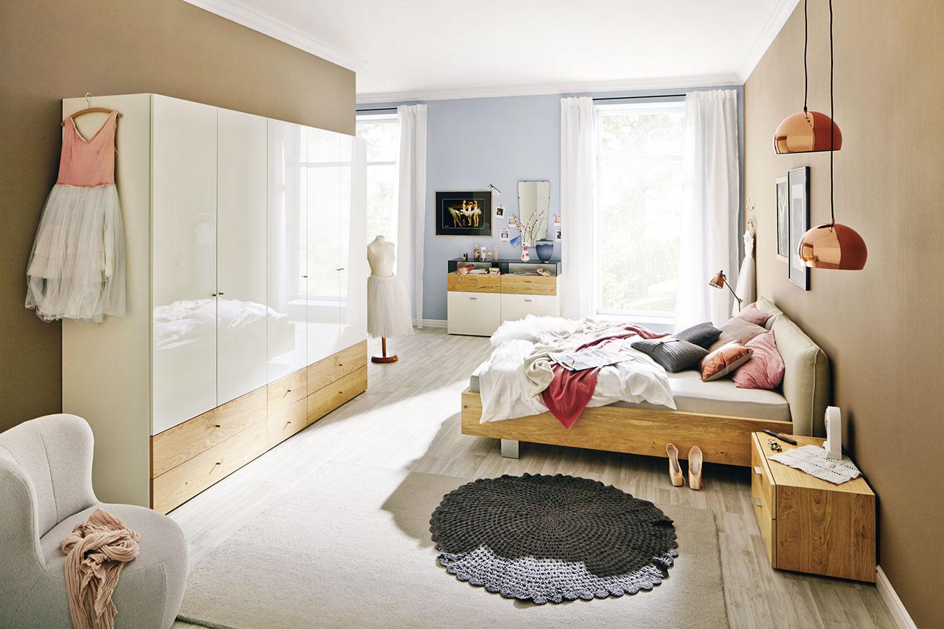Drevená konštrukcia postele ačalúnené čelo tvoria vkusné partnerstvo. Rovnaká farebnosť na nábytku priestor zjednotí, textílie amaľovka spálňu zútulnia. Nábytok nájdete vsortimente značky hülsta. (Predáva Merito.)