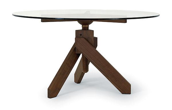 """VÝŠKOVO NASTAVITEĽNÝ stôl Vidun je nádherný, apredsa celkom banálny kúsok dizajnu. Jeho autor – taliansky dizajnér Vico Magistretti – ho vymyslel ako funkčnú zväčšeninu obyčajnej skrutky. Závit podstavy, ktorý sa dá vykrútiť do potrebnej vzdialenosti, je doplnený trojramennou konštrukciou so sklenenou doskou. """"Maticu"""" mu robí drevená trojnožka: spolu tak tvoria tesársky poctivý pár. Vyrába De Padova."""