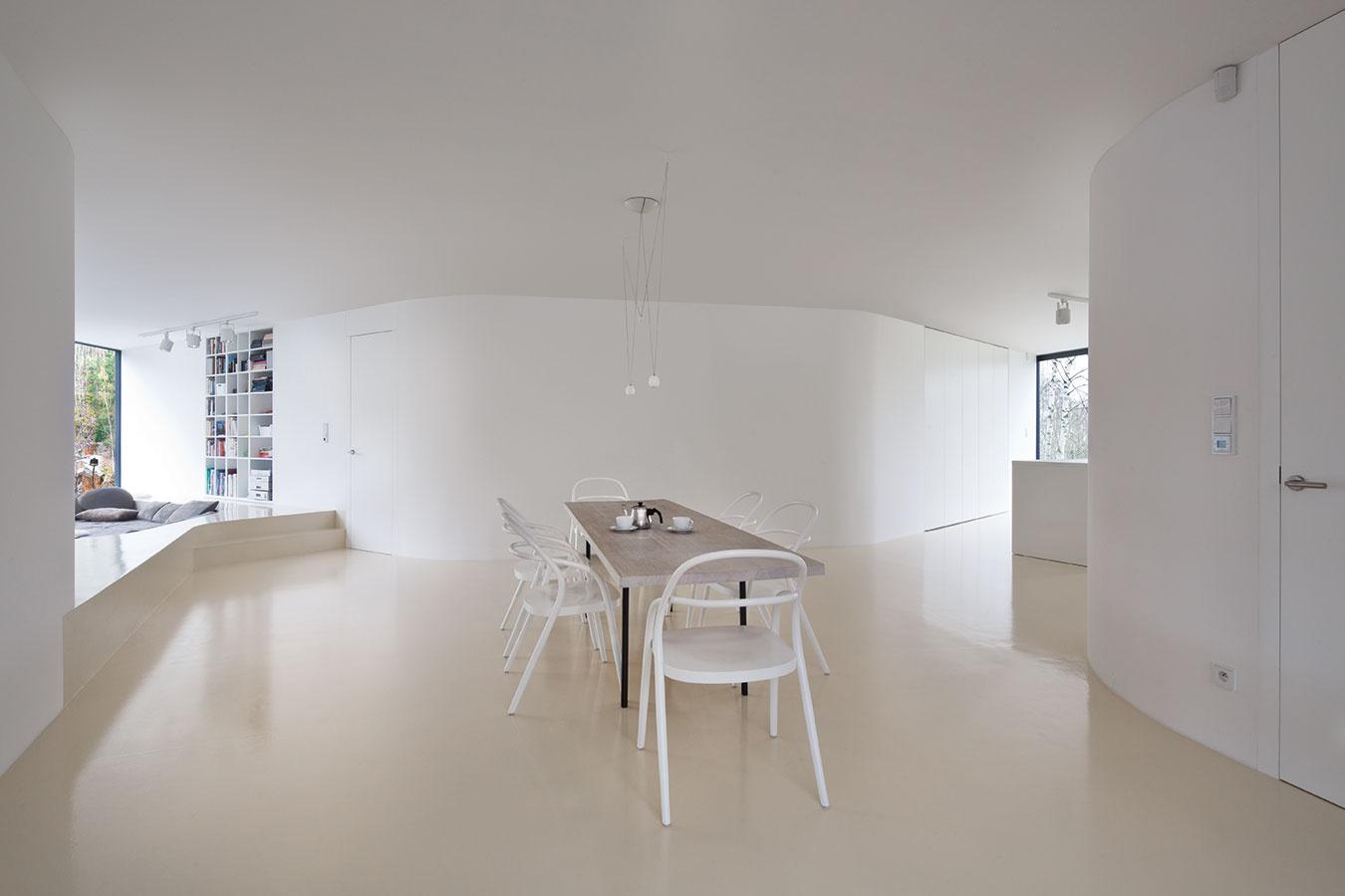 Biela interiéru jednoznačne dominuje – biele sú nielen steny apodlaha, ale aj police, stoličky čilampy. Dokonca aj drevená doska jedálenského stola vcentre dispozície je bielená.