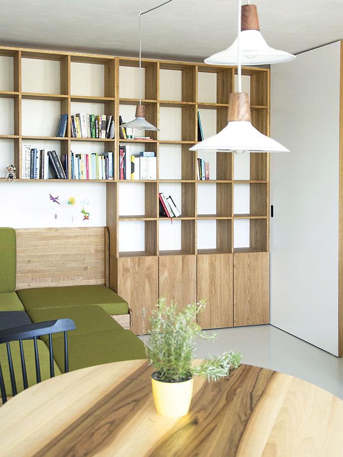 Oživujúcim prvkom dennej časti je zelené čalúnenie sedačky. Jej korpus je vyrobený zrovnakého dubového dreva ako knižnica aj časť kuchynskej linky, čo priestor zjednocuje.