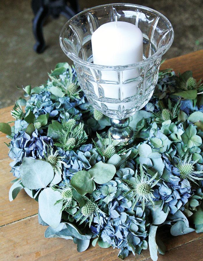 Venček zložený z kvetov hortenzie (Hydrangea), kotúča (Eryngium) a eukalyptu (Eukalyptus) môžete v interiéri aj zavesiť, no naozaj pekne ukáže, ak ho položíte na stôl alebo komodu a do jeho stredu umiestnite sviečku, prípadne ju vložíte do zaujímavého pohára na stopke. Aranžmán tak získa zaujímavý výškový rozmer.