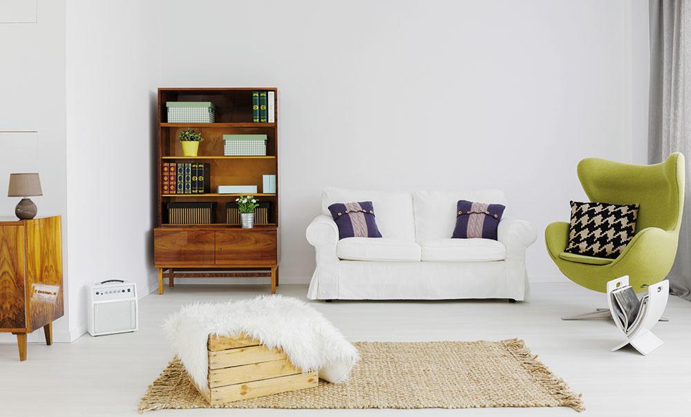"""Nábytok po babičke, sedačka z výpredaja a konferenčný stolík z banánov. Súhra obyčajných vecí. Prostorekosť takéhoto interiéru decentne """"učeše"""" plagát na stene, filodendron a lampa na vysokej nohe."""
