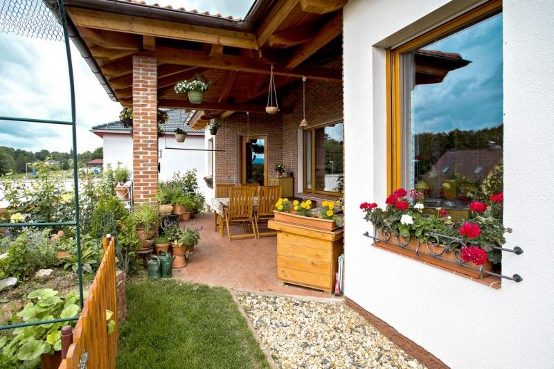 Ak to počasie dovolí, môže si rodina užívať vďaka posedeniu na zastrešenej terase krásne prostredie záhrady. V spodnej partii okna si všimnete ručne kované dekoratívne mriežky na kvetinové hrantíky.