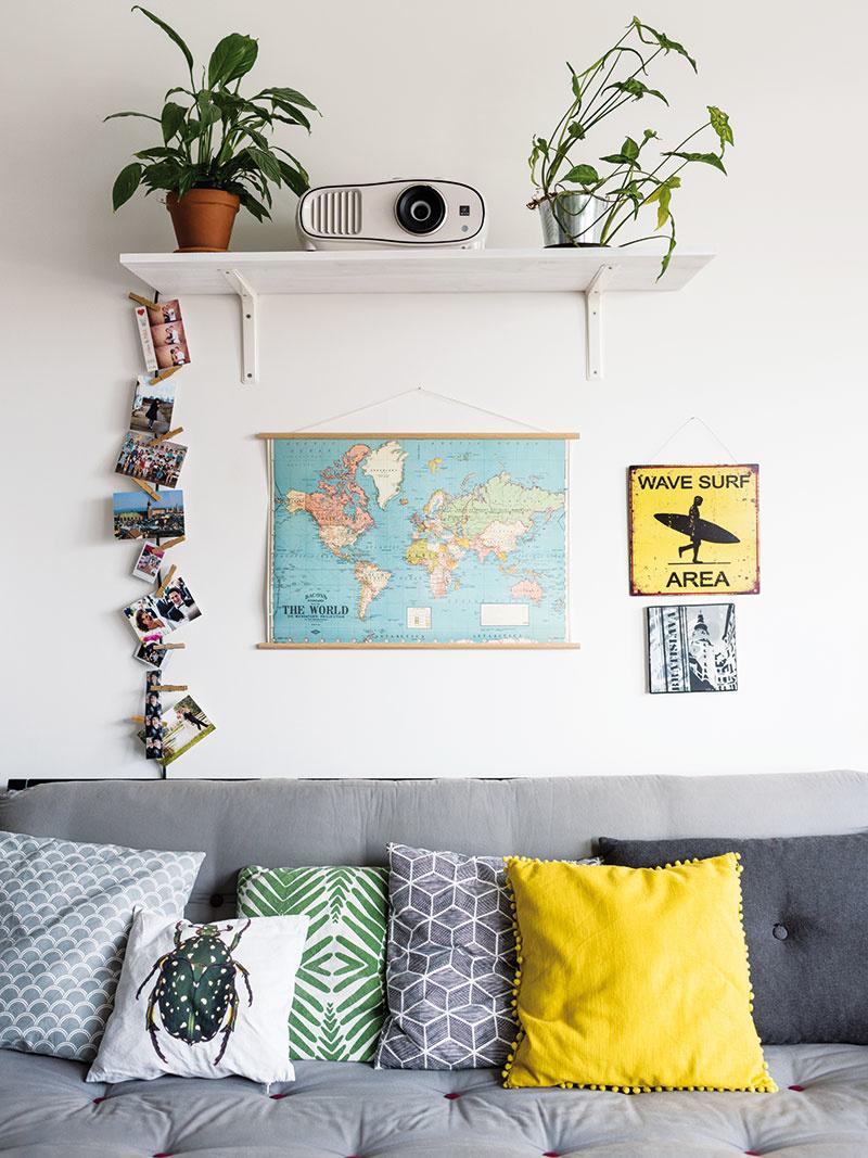Pomerne neutrálnemu interiéru, vktorom dominujú najmä odtiene sivej adrevo, dodávajú sviežosť doplnky adekorácie. Sedačku oživuje spleť vankúšov, priestor nad ňou mapa sveta afotografie zrôznych udalostí avýletov po svete.