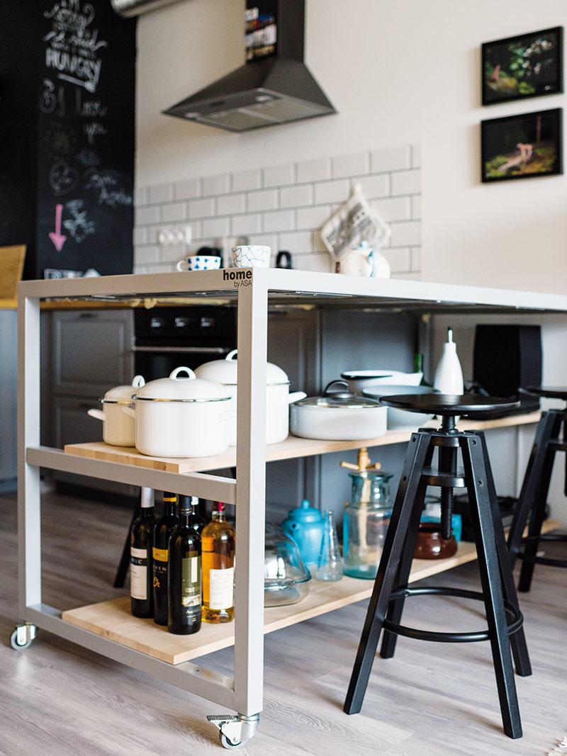 Pult na kolieskach, ktorý slúži ako jedálenský stôl, sa v minulosti používal na vystavenie bytových doplnkov. Strohú drevenú dosku nahradili vzorovaným obkladom.