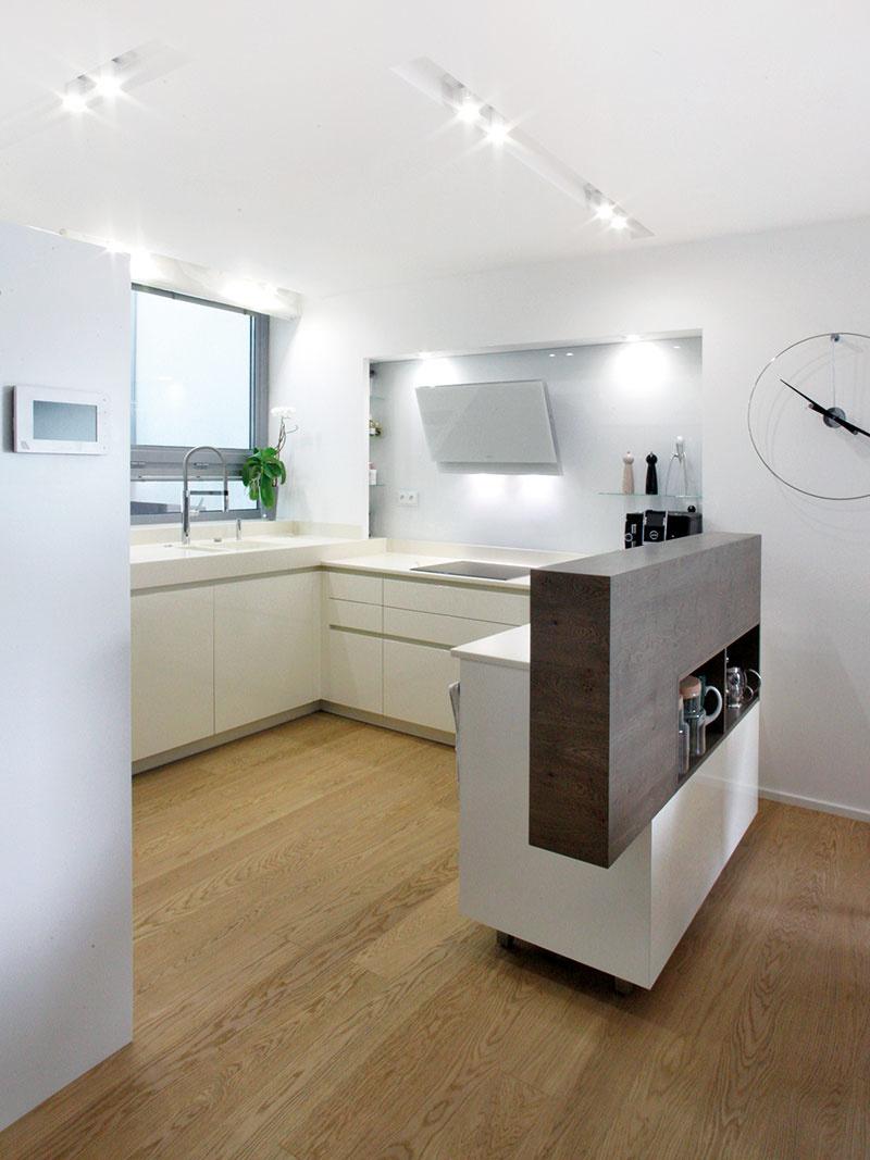 Z kuchyne orientovanej do vstupného patia vidno na vstup do domu, uličná fasáda, koncipovaná ako predsadená kulisa, tu však zároveň zabezpečila dostatok intimity.