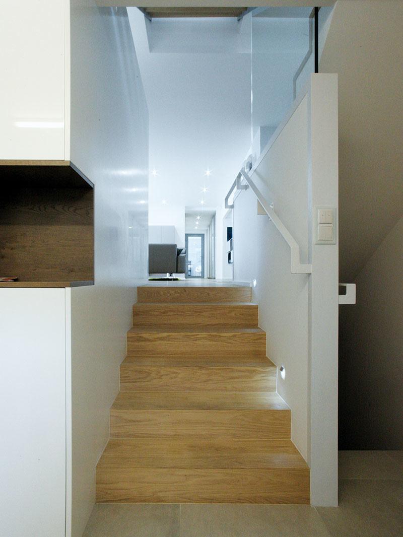 Z predsiene na úrovni ulice sa na vyvýšené hlavné obytné podlažie dostanete po niekoľkých drevených schodoch. Tu sa začína vertikálna komunikačná zóna – vždy po prekonaní jedného schodiskového ramena (výšky polovice podlažia) sa z nej otvárajú ďalšie priestory domu.