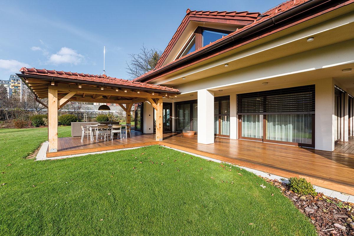Leto vzáhrade. Majitelia trávia vlete veľa času na zastrešenej terase. Jej súčasťou je aj pult obložený umelým kameňom, ktorý pri letných stretnutiach čiastočne nahrádza kuchyňu.
