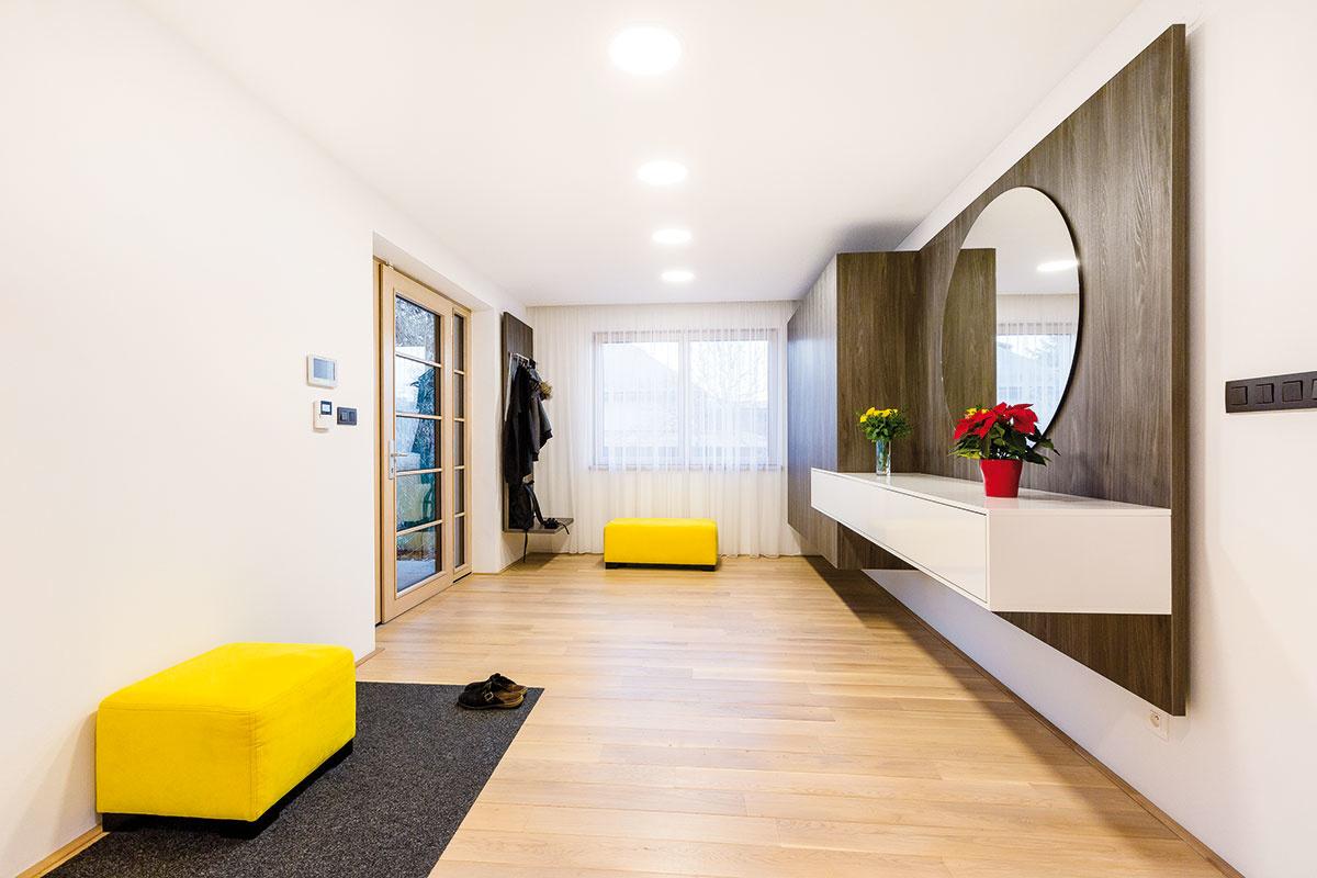 Vstupný priestor je spoločný pre obe samostatne fungujúce časti rozľahlého domu. Priam grafický základ interiéru spestruje niekoľko výrazných prvkov vživých farbách.