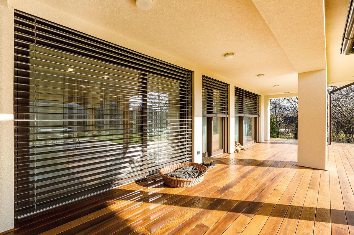 Drevohliníkové okná aportály sú doplnené vonkajšími žalúziami vrovnakom odtieni – účinne chránia interiér pred prehrievaním avzime znižujú tepelné straty. Navyše ponúkajú možnosť regulovať prístup denného svetla. Vspoločenskej zóne sa ovládajú na diaľku, vostatných miestnostiach manuálne.