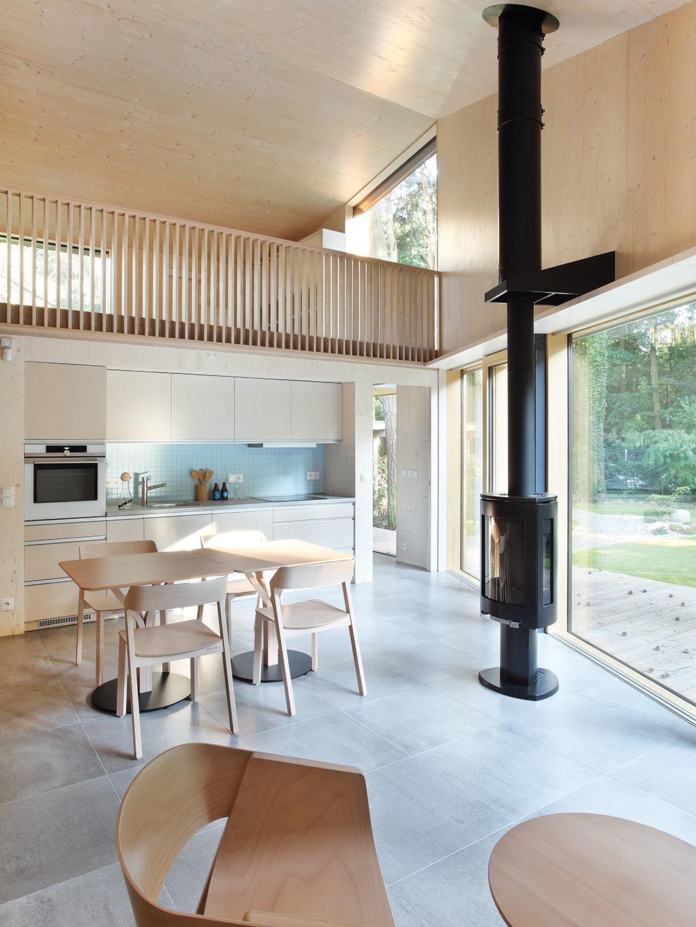 Kozubové kachle, ktoré sa starajú ovykurovanie celého objektu, sú umiestené takmer vcentre dispozície obývačky. Dopĺňajú pôsobivý výhľad avytvárajú zaujímavý kontrast kcelodrevenému interiéru.