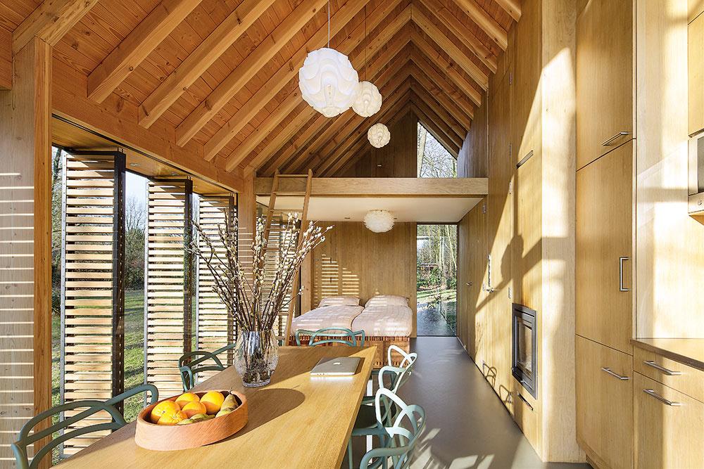 Jednoliaty interiér je otvorený až do krovu. Pôsobí veľmi vzdušne avďaka použitiu dreva aj útulne.