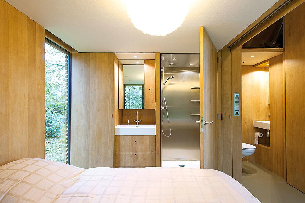 Stena zdubového dreva, ktorú zexteriérovej strany chráni plná bridlicová fasáda, ukrýva okrem bežných odkladacích priestorov aj kuchynskú linku atoaletu, vspacej časti zasa jednoduchú kúpeľňu.