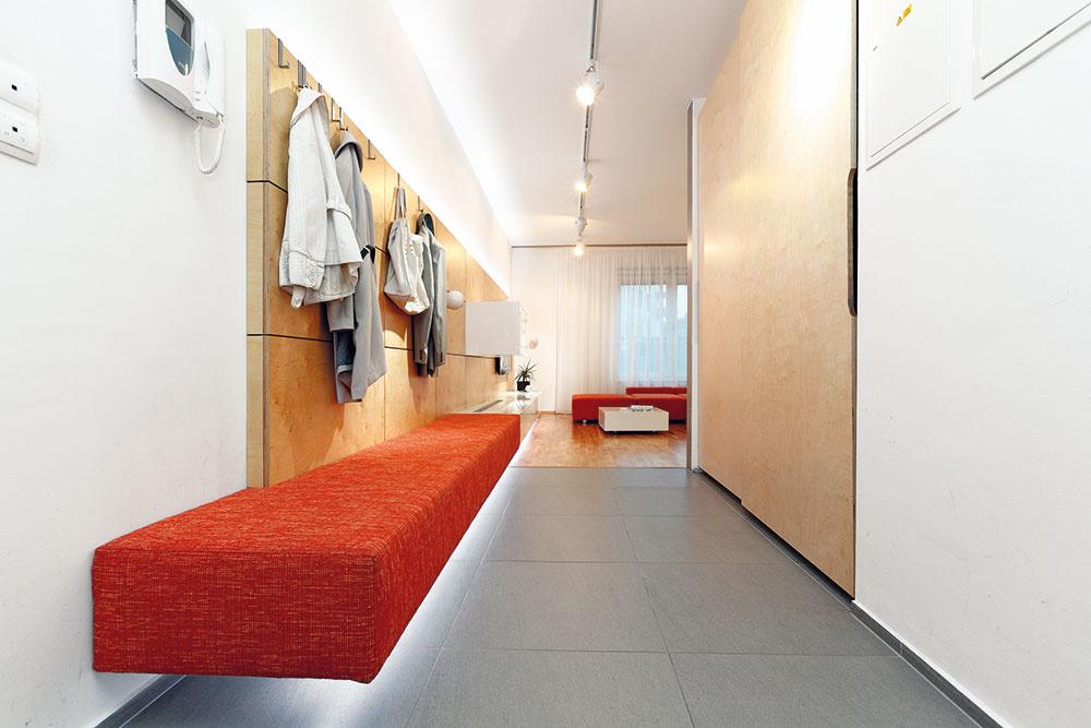 Prepojenie predsiene s obývačkou predstavuje zaujímavú možnosť, ako priestor opticky nafúknuť. Drevený obklad steny v návrhu architektov RULES plní v predsieni aj funkciu vešiaka, lavica na sedenie zase prechádza do skrinky na hifi súpravu a je materiálovo aj farebne totožná so sedačkou.