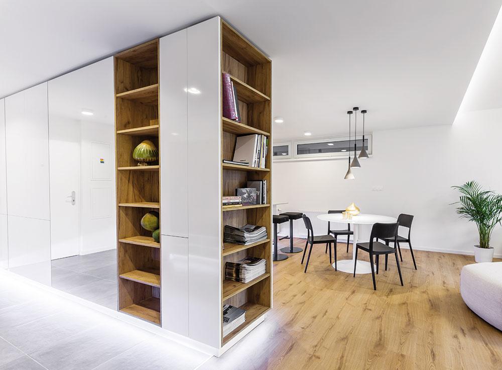 Priestorová skriňa, ktorá namiesto klasickej priečky oddeľuje predsieň akuchyňu, je originálnym nápadom apríjemným oživením otvoreného priestoru. Vobojstrannej skrini sú štedro dimenzované odkladacie priestory prístupné zo vstupnej chodby, zopačnej (kuchynskej) strany tvorí skriňu vysoký úložný blok so zabudovanými spotrebičmi.