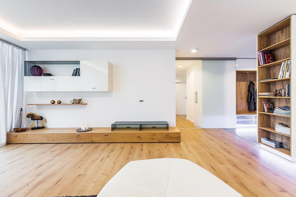 Svetelná rampa arôzne výšky podhľadu naznačujú votvorenom dennom priestore hranice obývačky.