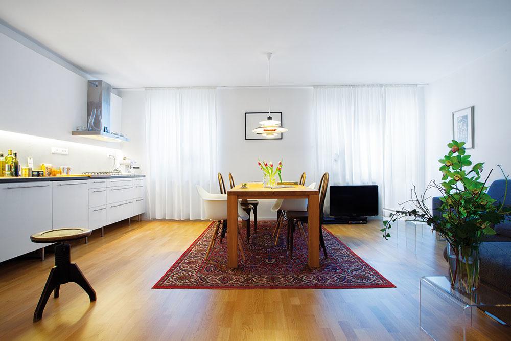 Centrom multifunkčnej obývačky, a tým aj celého bytu a života v ňom, je masívny dubový jedálenský stôl, pri ktorom sa často stretáva rodina aj priatelia.