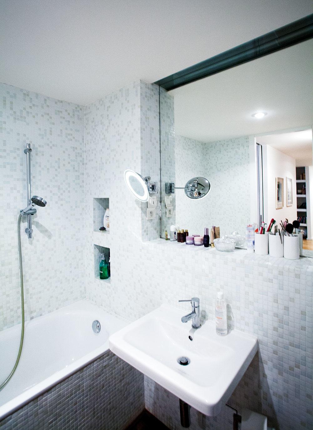Nová väčšia kúpeľňa vznikla zlúčením pôvodnej minikúpeľne a WC. Namiesto bežných keramických obkladačiek použili architekti na stenách jemnú mozaiku a stierku z pohľadového betónu.