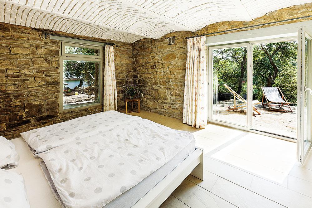 Vstodole na nachádzajú tri spálne. Tá spriamym vstupom na terasu pôvodne slúžila ako chliev. Po rekonštrukcii by ste pôvodné využitie tejto miestnosti skamennými stenami, krásnou valenou klenbou avýhľadom do sadu určite ani len nechyrovali.