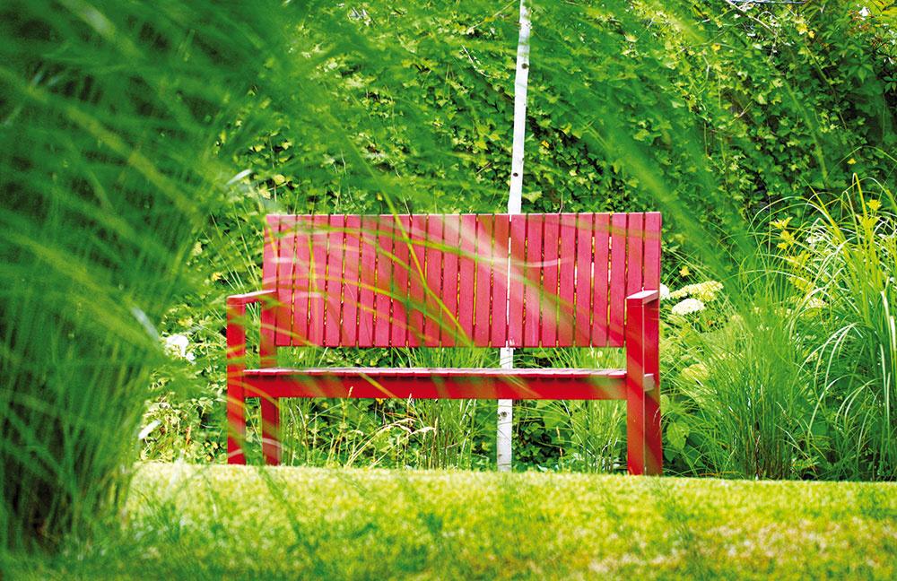 Farebný akcent môžete do záhrady vniesť pomerne jednoducho výberom záhradného nábytku. Do tejto minimalistickej architekti navrhli červené lavičky, ktoré ju vkusne dotvárajú.