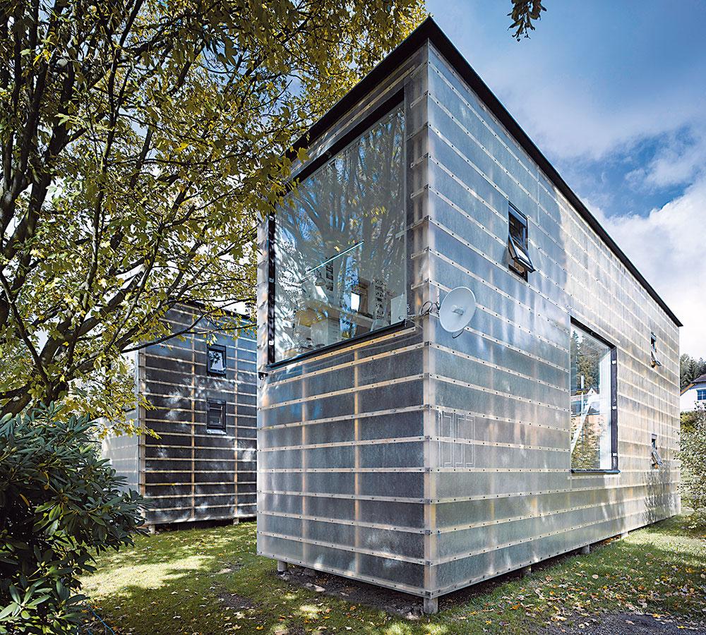 Fasáda, ktorá pôsobí ako jemná priesvitná vrstva, dáva tušiť konštrukciu domu – stavebné panely pokrýva sklolaminátový plášť.