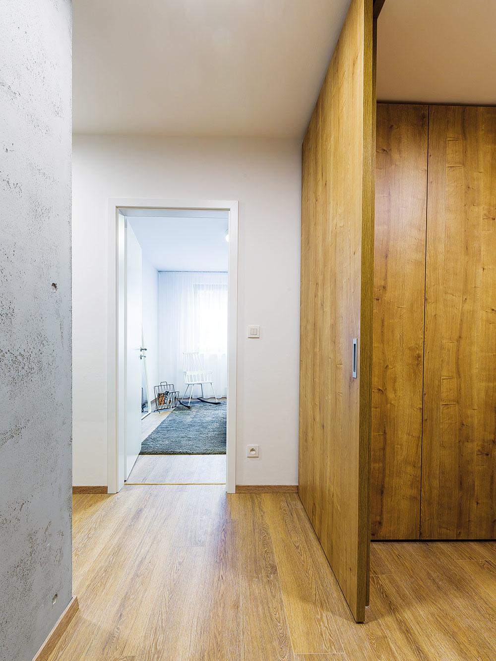 Prakticky aj štýlovo. Zveľkorysej vstupnej haly oddeľuje vložená drevená konštrukcia praktický šatník amalé zádverie smiestom na prezutie aodloženie kabátov. Keď sa zatvoria posuvné dvere na celú výšku miestnosti, ostane len príjemne pôsobiaca elegantná drevená stena.