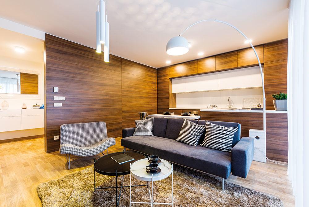 Recept na prirodzené začlenenie kuchyne do obytného priestoru, ktorý uplatnili architekti vtomto byte, znie: bezúchytkové otváranie skriniek, ktoré zmení linku na jednoliatu stenu bez lesa držadiel, apôsobivé elegantné materiály. Dyhu svýraznou kresbou využili nielen na hladkom povrchu linky, ale aj na ďalšej stene obývačky, čím sa dve zóny príjemne prepojili apriestor sa opticky zjednotil.