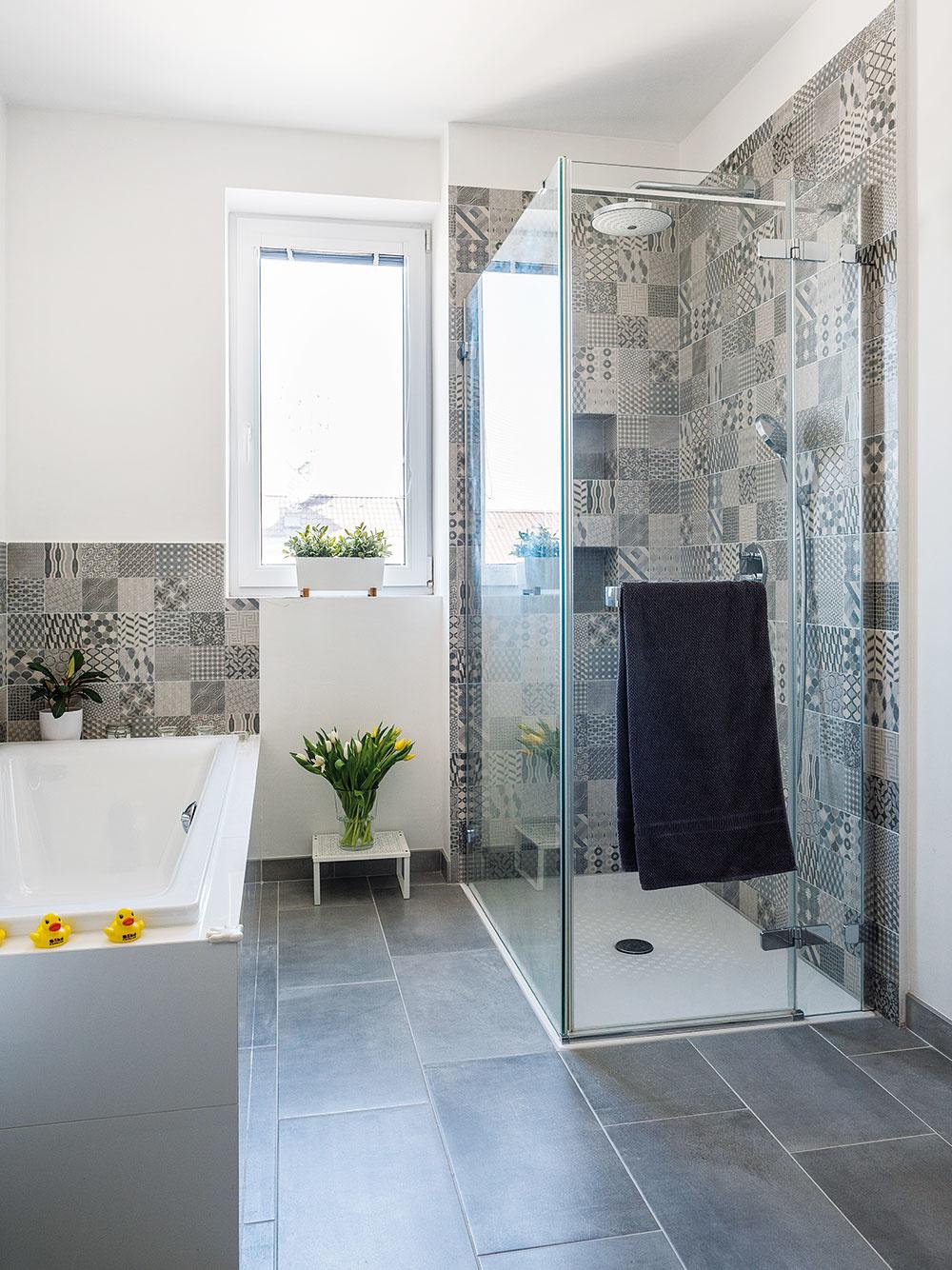 Šikovné riešenie. Kúpeľňa soknom patrila kprednostiam pôvodného bytu. Zmestila sa sem vaňa aj sprchovací kút svaničkou vúrovni podlahy. Vetracie potrubie skryli za predsadenú stenu snikami, ktoré majú vsprchovacom kúte praktické využitie.