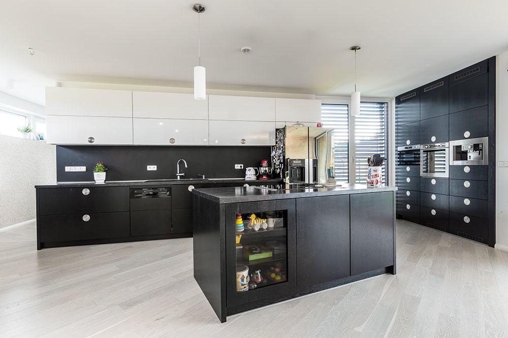 Čierno-biela kuchyňa je optimálne rozvrhnutá aprepojená sjedálňou. Pracovnú linku akuchynský ostrov dopĺňa solitérne umiestnený bočný panel so vstavanými spotrebičmi značky Whirlpool.