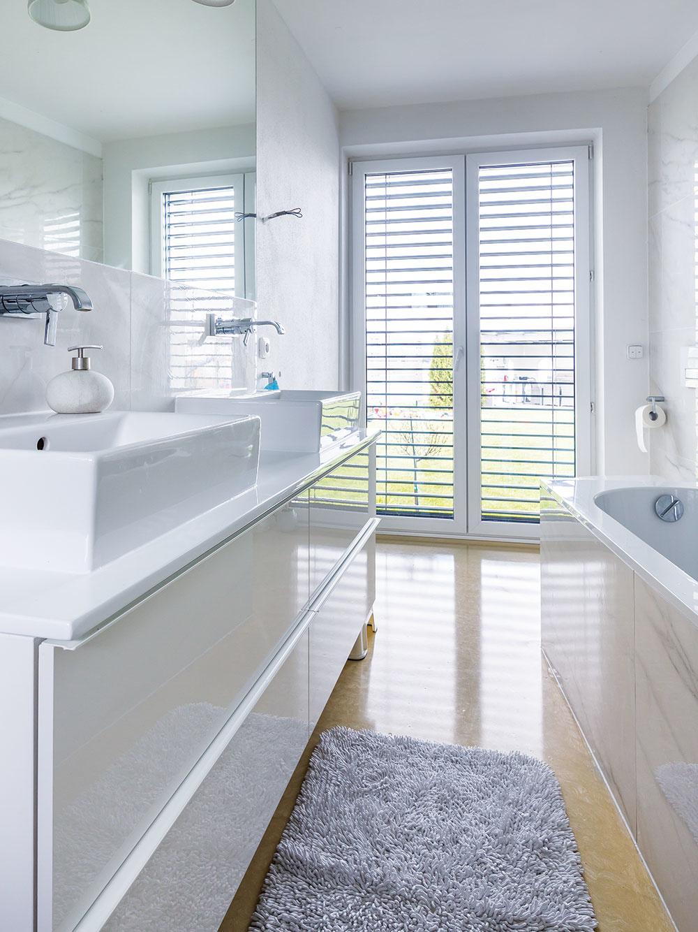 Kúpeľňa vbielej farbe sliatou béžovou podlahou pôsobí čisto aútulne.