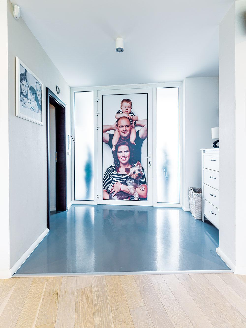 Liata podlaha účelne dotvára jednoduchý vstup, ktorý si majitelia oživili rodinnou fotografiou umiestnenou na vchodových dverách. Vľavo je prechod do hospodárskej časti domu agaráže.