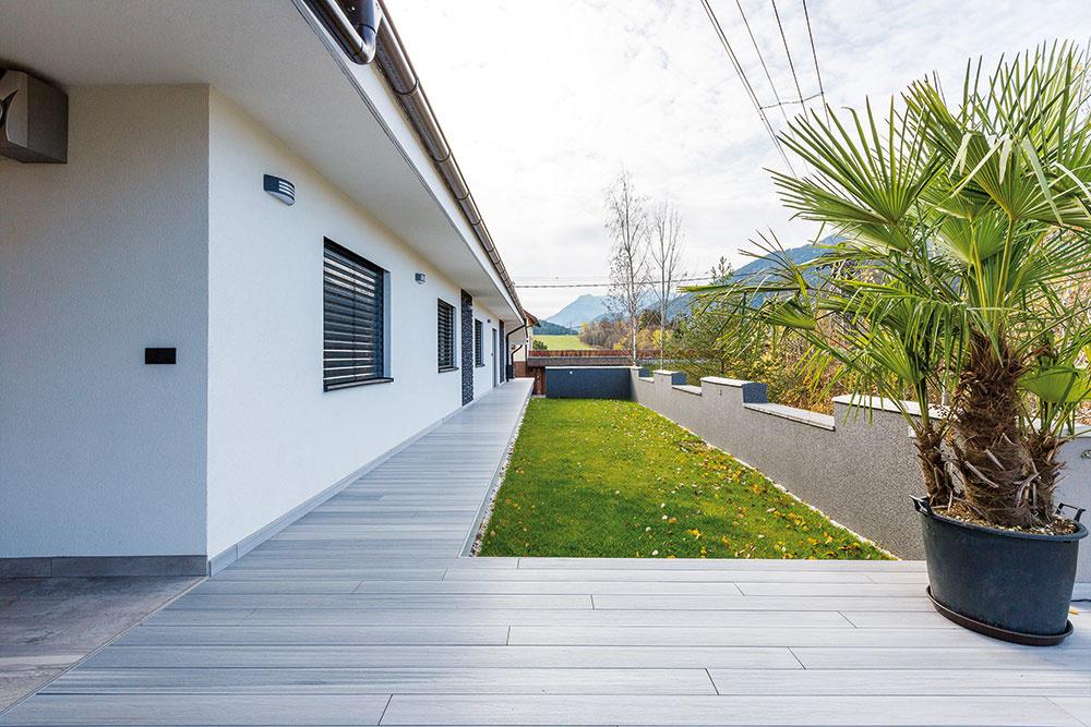 Chránená terasa za domom je prístupná znočnej zóny. Včasti pred spálňou majiteľov ju príjemne dopĺňa vírivka, ktorej intimitu zabezpečuje drevená stienka.
