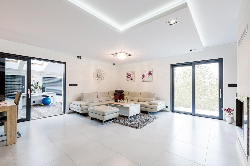 Veľkoformátová dlažba vsvetlom béžovom odtieni prepája interiéry vcelom dome svýnimkou zimnej záhrady. Oto, aby bol dotyk nôh sdlažbou príjemný, sa stará podlahové kúrenie.