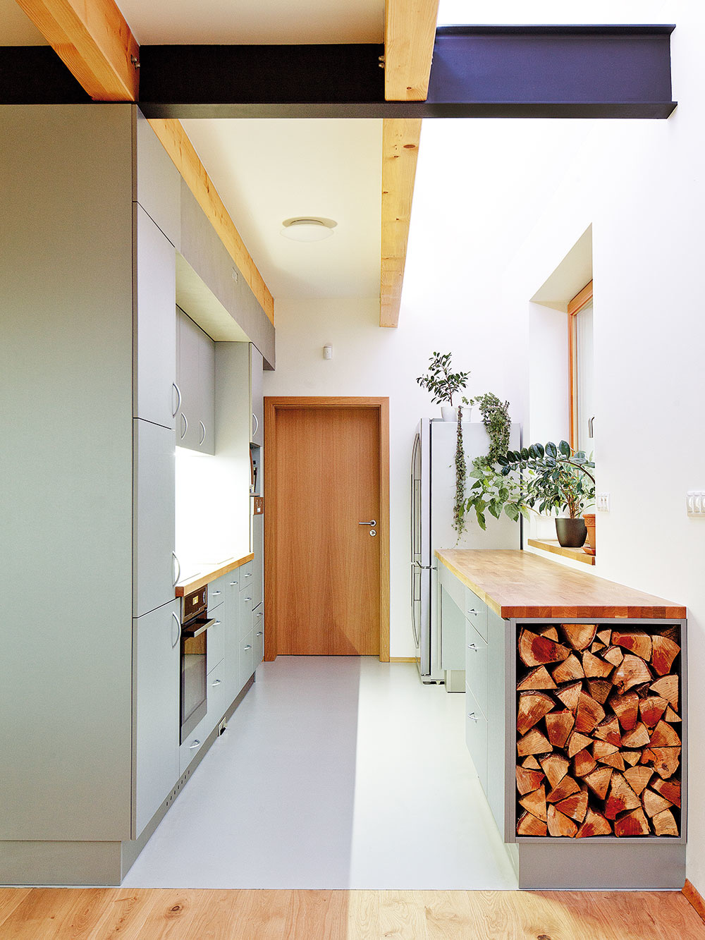 Rovnaké materiály hrajú dôležitú úlohu v exteriéri aj interiéri, efektne vyriešený je izásobník na drevo.