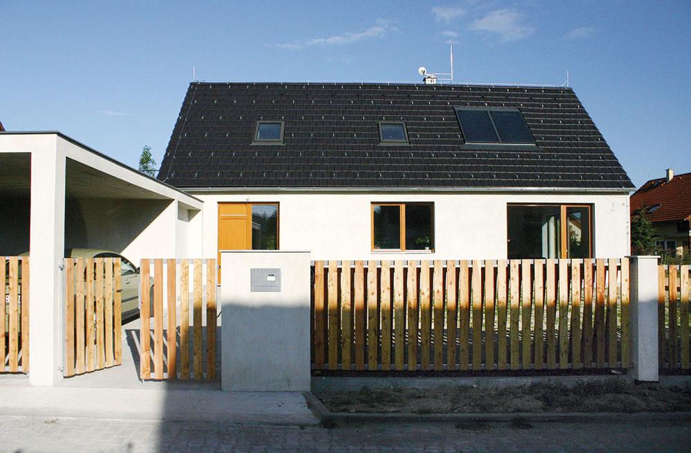 Hlavný vstup do domu zbočnej strany je typickým znakom ľudovej architektúry, rovnako ako drevený latkový plot.