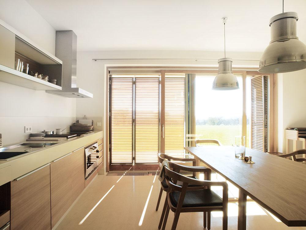 Rovnako jednoduché, nenásilné afunkčné ako exteriér usadlosti sú aj interiéry nového rodinného domu. Zasklené dvere nielen sprístupňujú terasu, ale otvárajú aj mimoriadny výhľad zobytných priestorov.