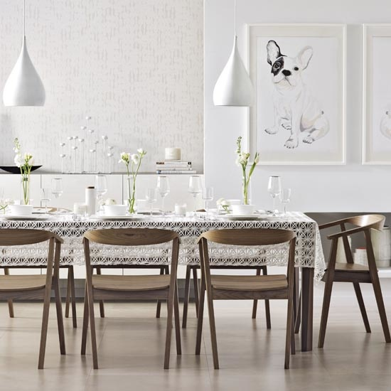 Modern white dining room, Scandi style wooden dining table and chairs, delicate lace table cloth, low hanging white pendant lights, wall mounted portraits of white boxer dog with black eye patch, laminate flooring, IH 09/2013 Pub Orig
