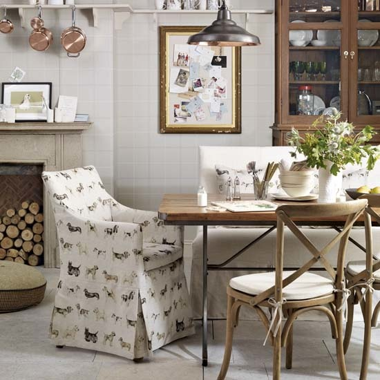 Traditional country style dining room, fireplace with firewood storage, stone flooring, wooden dining table, mismatching chairs with fabric chair covers, low hanging copper pendant light, wooden dresser, IH 11/2013 Pub Orig