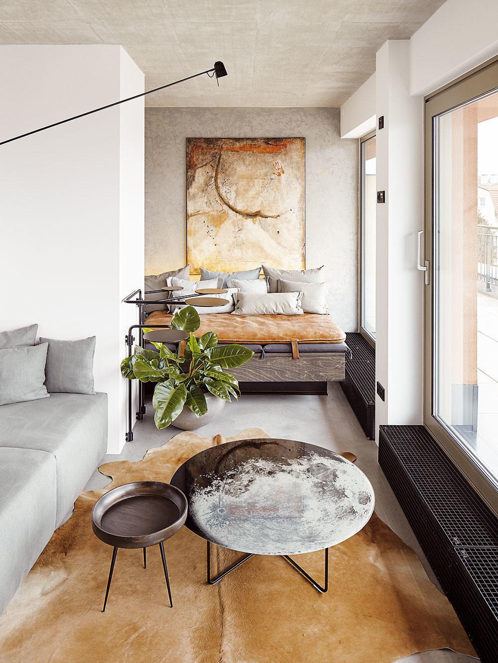 Všetky prvky v interiéri spolu ladia štýlom, farebne imateriálovo – betónová stierka na podlahe, stena s patinovou maľovkou, hovädzie kože, gauč s koženou žinenkou, obraz ikonferenčný stolík značky Diesel.