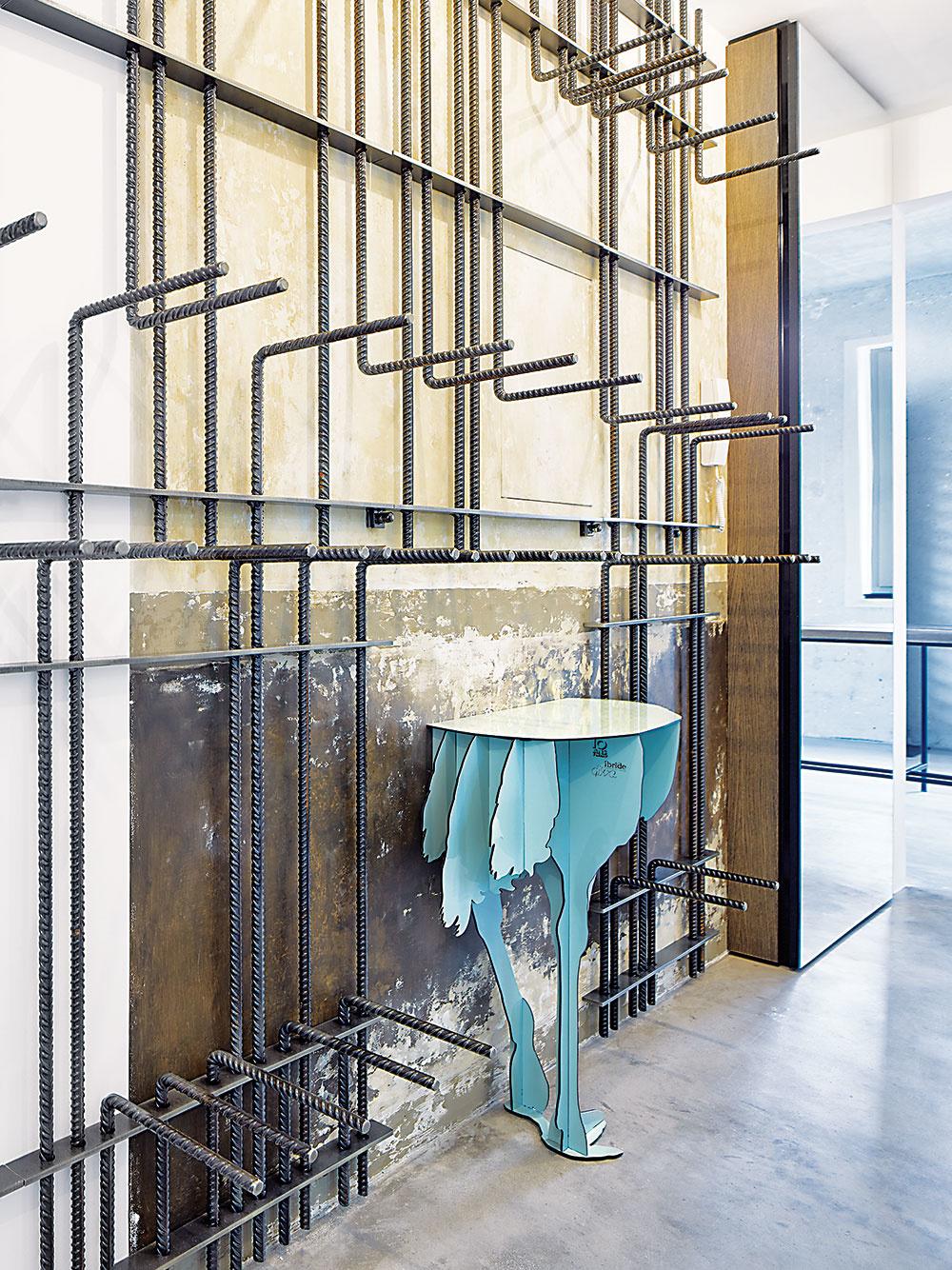 Do bytu sa dá priviezť výťahom – vešiak z betonárskej výstuže a pštrosie torzo sú prvé výrazné prvky, ktoré uvidíte, keď sa otvoria jeho dvere. Stolík v chodbe pochádza z dielne francúzskych dizajnérov Ibride.