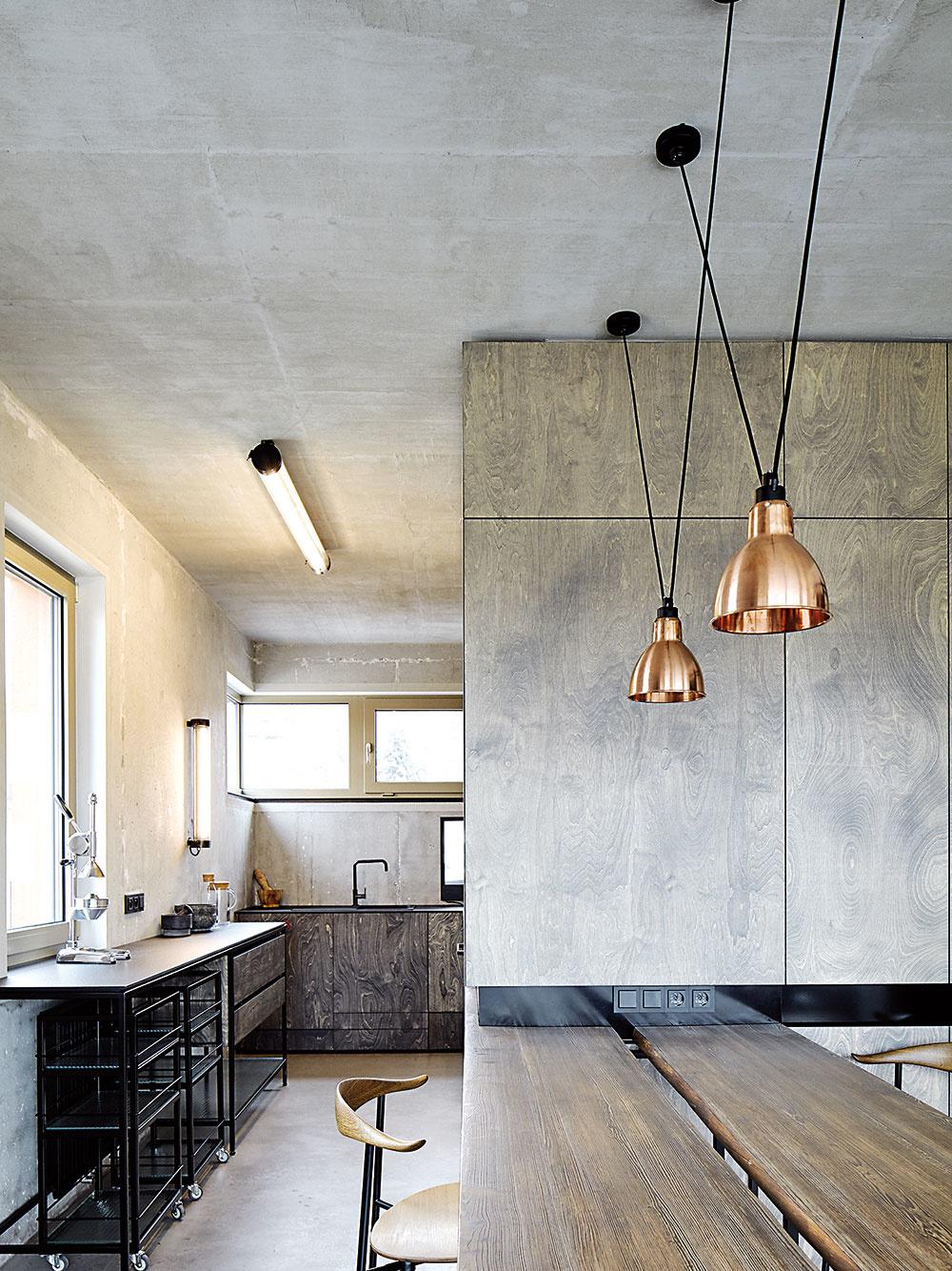 Kuchyni jednoznačne vládne betón. Jednoduchú linku v odtieňoch sivej osvetľujú industriálne ladené nástenné svietidlá Polaboy.