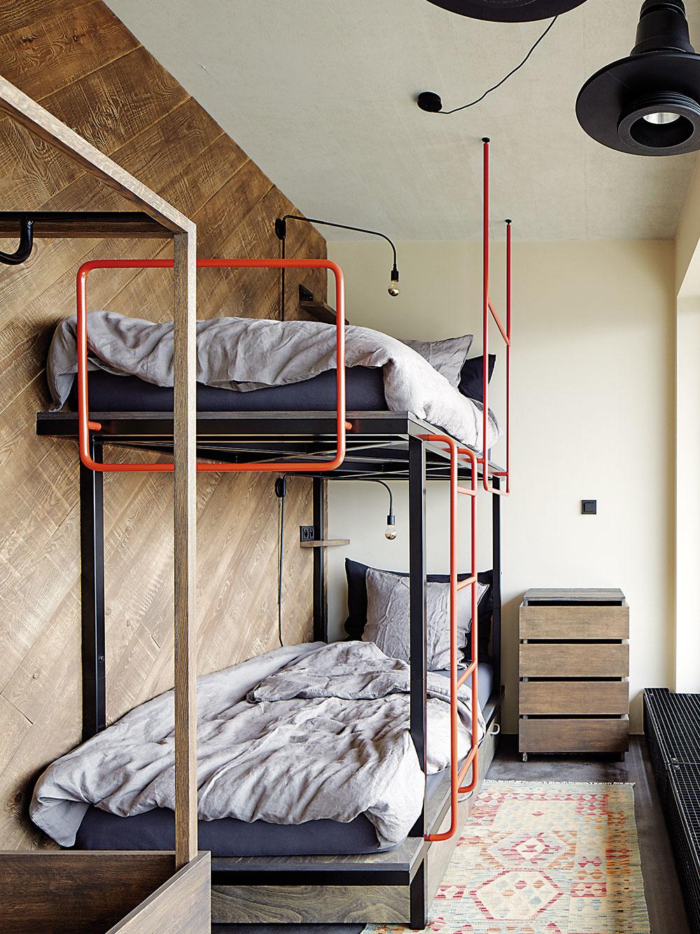 Poschodová posteľ so zábradlím aschodíkmi znaoranžovo natretých rúrok patrí k originálnym prvkom, navrhnutým na mieru.