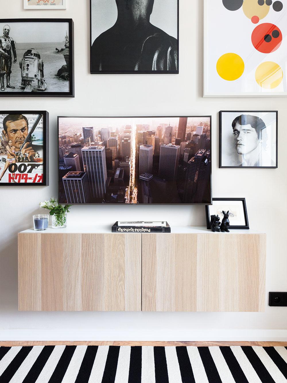 STENA V OBÝVAČKE PREZRÁDZA, že majiteľ bytu je milovníkom filmov. Z čiernych a bielych rámov sa na neho usmieva Arnold Schwarzenegger či filmový James Bond.