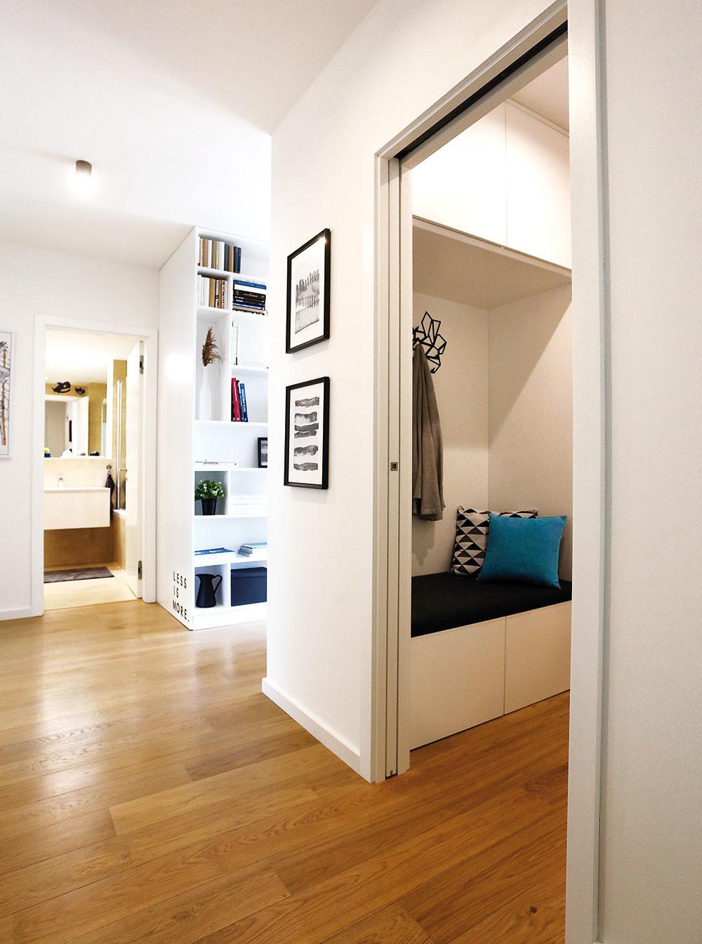 """Praktický šatník s posuvnými dverami, ktoré sa zasúvajú do puzdra v stene, """"ukrojil"""" kúsok z pomerne rozľahlej chodby. Aj vďaka tomu, že je tu dostatok miesta na odloženie všetkého, čo s domácnosťou súvisí, môže byť celý byt minimalistický a vždy uprataný."""